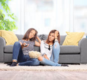 Två borrade tonårs- flickor som håller ögonen på TV Arkivfoto