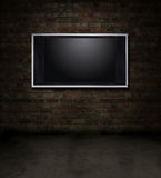 TV brick room. Dark grungy red brick room with a flat screen TV Stock Image