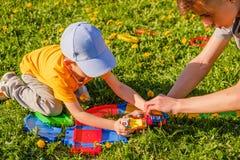 Tv? broderlekar med en leksakbil p? gr?smattan f?r gr?nt gr?s royaltyfri foto