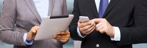 Två businesspeople med smartphone- och minnestavlaPC Arkivbilder