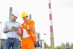 Två byggnadsarbetare som diskuterar över minnestavlaPC på bransch Arkivfoton