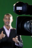 TV Camera lens and Viewfinder. Close-up of a television camera viewfinder and lens with a presenter out of focus in the background. Viewfinder display added in royalty free stock photos