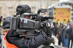 TV camera man filming a political event. Vilnius, Lithuania - April 15, 2018: TV camera man filming a political event in Vilnius on April 15, 2018. Vilnius is Royalty Free Stock Images