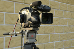 TV camera on tripod without people. TV camera on tripod against a street wall Stock Image
