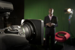 TV Camera zoom lens. Foreground television camera zoom lens with a presenter out-of-focus in the background Stock Photos