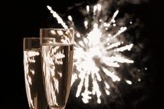 Två Champagneexponeringsglas på nattfyrverkerier Arkivbild