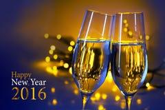 Två champagneflöjter mot blått gulnar bakgrund, lycklig text Arkivfoton