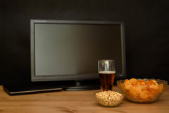 TV and computer with unhealthy snack on table isolated on black Royalty Free Stock Photography