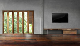 Tv on concrete wall with tall windows in old wooden floors empty room stock photography
