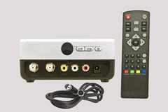 TV Converter. Box on light gray background with front and rear view,coax cable,and remote control Stock Images