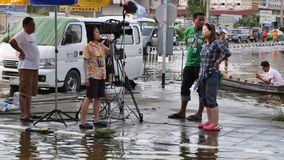 A TV crew is in a flooded street of Pathum Thani, Thailand, in October 2011.  Stock Image