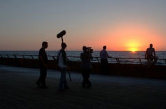TV crew at sunset. TV crew filming a scene at sunset on the seashore royalty free stock images