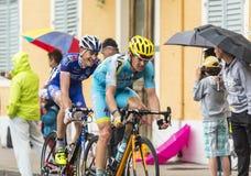 Två cyklister som rider i regnet Arkivfoton
