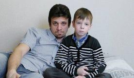 TV de observación que miente en el sofá El muchacho aburrido y su papá están mirando la TV y los interruptores los canales Imagenes de archivo