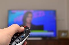 TV de observación y usar el control remoto Imagenes de archivo