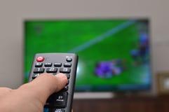 TV de observación y usar el control remoto Imagen de archivo