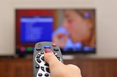TV de observación y usar el control remoto Imagen de archivo libre de regalías
