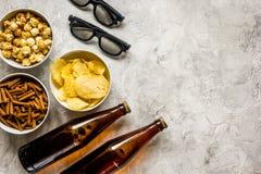 TV de observation avec les frites, la bière et les verres 3D sur la vue de bureau en pierre Photos libres de droits