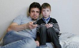 TV de observation se trouvant sur le divan Le garçon ennuyé et son papa observent la TV et les commutateurs les canaux Photos libres de droits