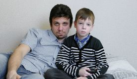 TV de observation se trouvant sur le divan Le garçon ennuyé et son papa observent la TV et les commutateurs les canaux Images stock