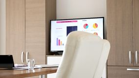 TV that dispalys graphs and data about a company in empty meeting board room. Dolly footage stock footage