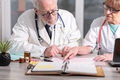 Tv? doktorer som diskuterar om medicinska resultat royaltyfria bilder