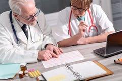 Tv? doktorer som diskuterar om medicinska resultat royaltyfri foto