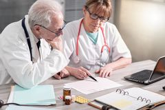 Tv? doktorer som diskuterar om medicinska resultat royaltyfri fotografi