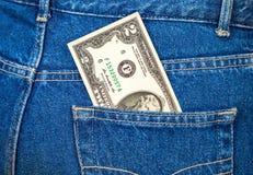 Två dollar räkning som klibbar ut ur jeansfacket Arkivfoto
