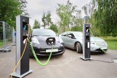 Två elbilar som laddas upp på elektrisk uppladdning Arkivfoton