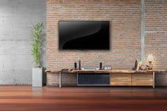 TV en la pared de ladrillo roja con la tabla de madera Imagen de archivo