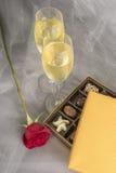 Två exponeringsglas av Champagne, den enkla röda rosen och en öppen ask av gourmet- choklader #3 Royaltyfria Bilder