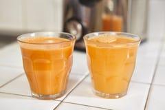 Två exponeringsglas av morotfruktsaft Arkivfoton