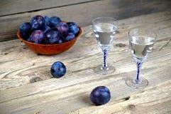 Två exponeringsglas av plommonkonjak med plommoner Arkivfoto