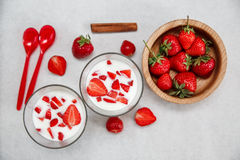 Två exponeringsglas av yoghurt, röda nya jordgubbar är i träplattan med plast- skedar, kanel på vitboken Frukost eller Royaltyfri Foto