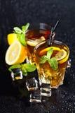 Tv? exponeringsglas med kallt traditionellt med is te med citronen, mintkaramellsidor och iskuber royaltyfri fotografi