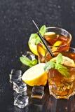 Tv? exponeringsglas med kallt traditionellt med is te med citronen, mintkaramellsidor och iskuber arkivbild