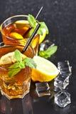 Tv? exponeringsglas med kallt traditionellt med is te med citronen, mintkaramellsidor och iskuber royaltyfria bilder