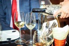Två exponeringsglas processen av att hälla vinet blind avsmakning Arkivfoto