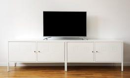 TV för bred skärm på den vita ställningen nära den ljusa väggen arkivbilder