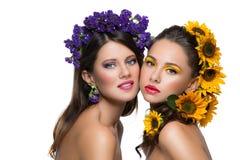 Två flickor med blommor i hår Fotografering för Bildbyråer