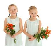 Två flickor med buketter av blommor Fotografering för Bildbyråer