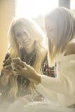 Två flickor som har gyckel, medan dricka kaffe Royaltyfria Foton