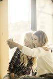 Två flickor som har gyckel, medan dricka kaffe Royaltyfria Bilder