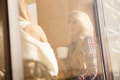 Två flickor som har gyckel, medan dricka kaffe Royaltyfri Bild