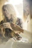 Två flickor som har gyckel, medan dricka kaffe Royaltyfri Foto