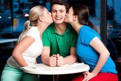 Två flickor som kysser den stiliga unga pojken Arkivfoton