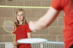 Två flickor som spelar badminton i skolaidrottshall Arkivfoton