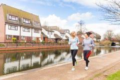Två flickor som utomhus joggar i London Arkivfoton