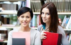 Två flickvänner med böcker Fotografering för Bildbyråer